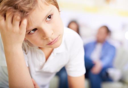 niños tristes: Retrato de muchacho serio en el fondo de sus padres Foto de archivo