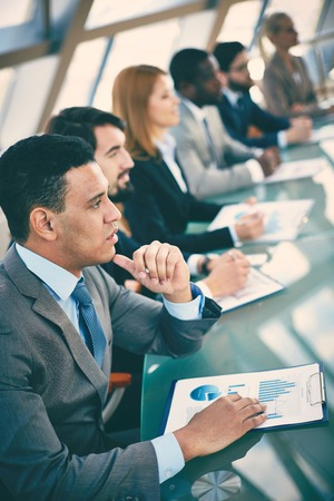 sessions: Pensive young businessman listening to explanations at seminar on background of other listeners Stock Photo
