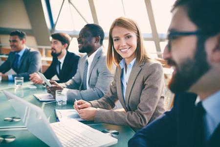 Rad av affärsmän lyssnar på presentation vid seminarium med fokus på leende kvinna tittar på kameran Stockfoto