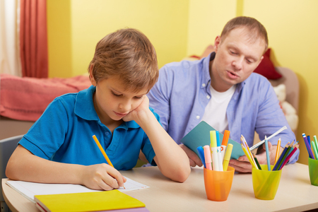 schoolwork: Portrait of cute schoolboy and his father making schoolwork at home