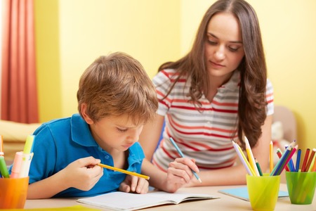 schoolwork: Portrait of cute schoolboy and his mother making schoolwork at home Stock Photo