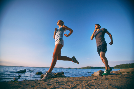 activewear: Photo of happy young dates running down coastline in the morning