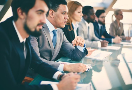 listeners: Pensive young businessman listening to explanations at seminar surrounded by other listeners Stock Photo