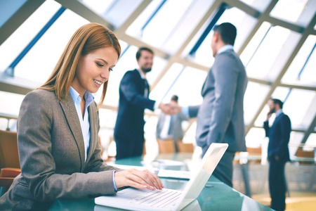 executive woman: Pretty businesswoman networking or planning work on background of colleagues handshaking Stock Photo