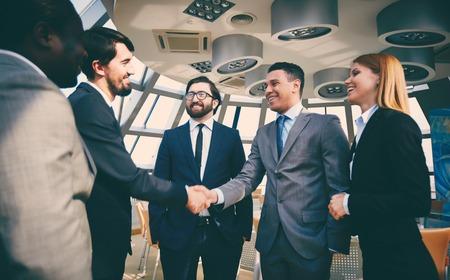 Groep van mensen uit het bedrijfsleven te kijken naar hun collega's handshaking na opvallende grote deal Stockfoto