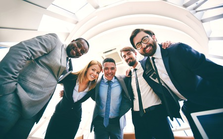 Group of successful business people in suits looking at camera photo