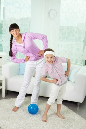 floor standing: Portrait of little girl and her mother doing physical exercise at home Stock Photo