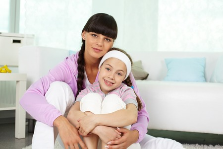 families together: Portrait of happy girl and her mother in sportswear looking at camera at home