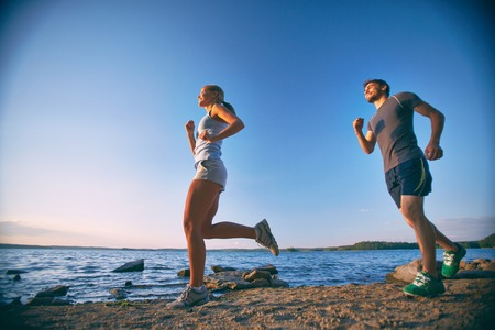 activewear: Photo of happy young dates running down coastline
