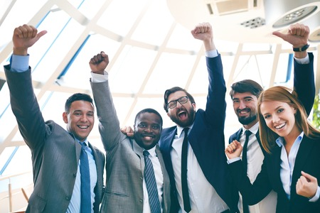 arms raised: Group of ecstatic business partners looking at camera with raised arms