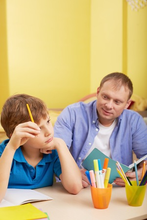 schoolwork: Portrait of pensive schoolboy and his father making schoolwork at home Stock Photo
