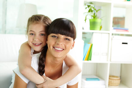 young schoolgirl: Portrait of happy girl and her mother looking at camera with smiles