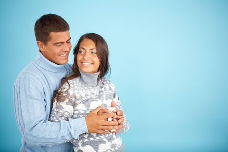 pullovers: Portrait of happy couple in fashionable pullovers posing against blue background  Stock Photo