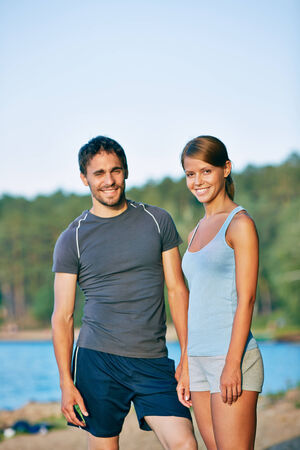 activewear: Photo of young sporty couple in activewear looking at camera outdoors