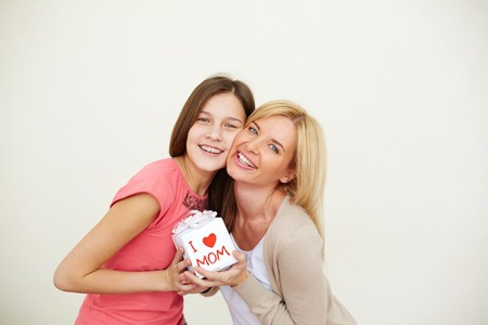 Teenage girl and her mom with small present looking at camera in isolation