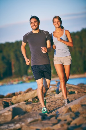Photo of happy young couple running outdoors photo