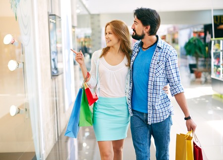 customer relationship: Portrait of young couple shopping in the mall