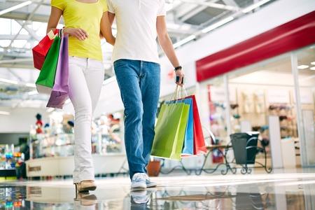 Benen van de jonge paar gaan in het winkelcentrum Stockfoto
