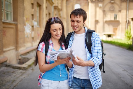 Couple of travelers studying map of ancient town photo