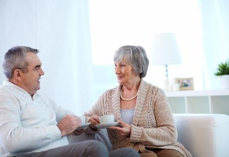 amigas conversando: Imagen de una pareja de jubilados bebiendo té y hablando en su casa