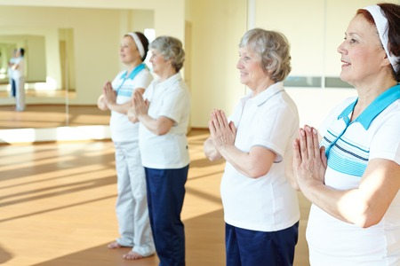 Portrait of two aged females doing yoga exercise for balance in sport gym  photo