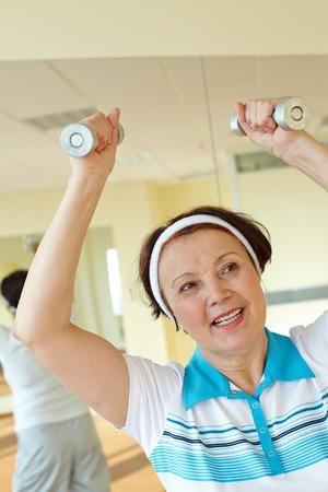 physical activity: Portrait of aged woman doing physical exercise with barbells