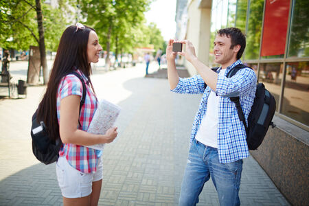 taking a wife: Happy young man taking photo of his wife or girlfriend during journey