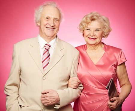 Portrait of a charming retired couple posing against pink background photo