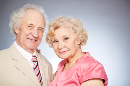 Portrait of a charming retired couple looking at camera in isolation photo