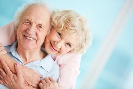 Gelukkig en aanhankelijk bejaarde echtpaar kijken naar de camera