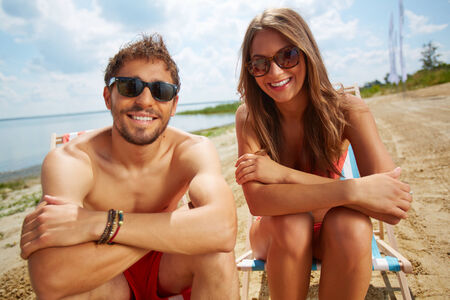 Relaxed young lovers sitting on the beach on a sunny day photo