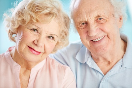 looking at viewer: Close-up portrait of a charming elder couple looking at the viewer with a smile