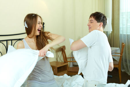 Happy young couple playing with pillows in bed photo
