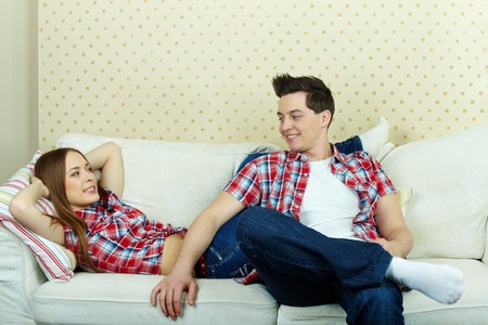 Happy couple in casual clothes having rest on sofa  photo