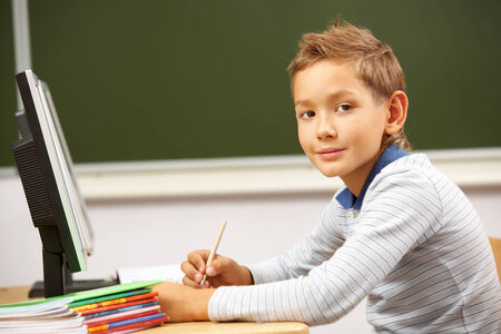 lad: Portrait of smart lad by the desk looking at camera
