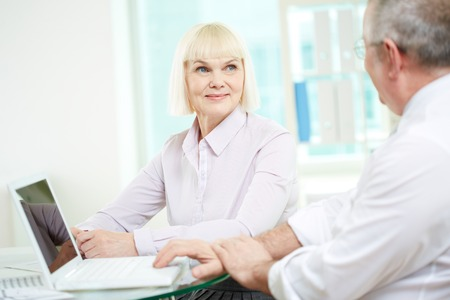 Portrait of happy mature businesswoman looking at her partner during discussion Stock Photo - 29939176