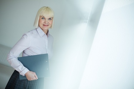 Portrait of mature businesswoman with clipboard looking at camera in office Stock Photo - 29939197