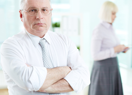 Portrait of serious boss looking at camera with female standing on background Stock Photo - 29939174