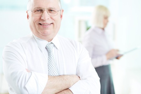 Portrait of smiling boss looking at camera with female standing on background Stock Photo - 29939175