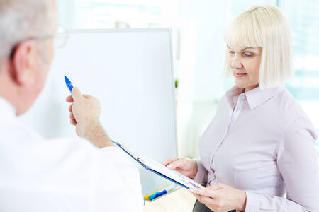 Image of mature businesswoman listening to her partner making presentation on whiteboard at meeting Stock Photo - 29939195
