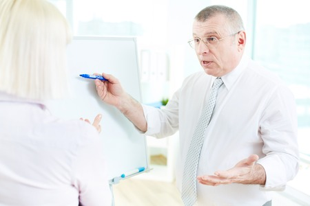 Image of mature businessman teaching his partner on whiteboard at meeting Stock Photo - 29939199