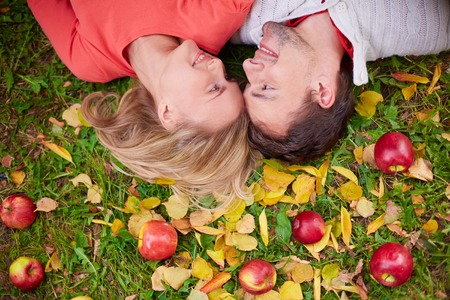 Happy young couple looking at one another while lying on ground with red apples and yellow leaves on it photo