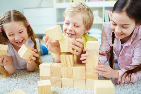 play blocks: Three little friends playing with wooden bricks