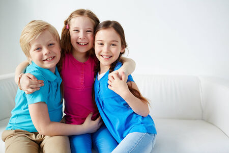 kids hugging: Three little friends looking at camera with smiles  Stock Photo
