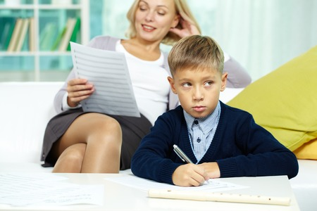 private schools: Portrait of diligent pupil with musical notes on paper near by and his tutor on background Stock Photo