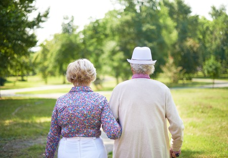Back view of serene senior couple taking a walk in the park photo