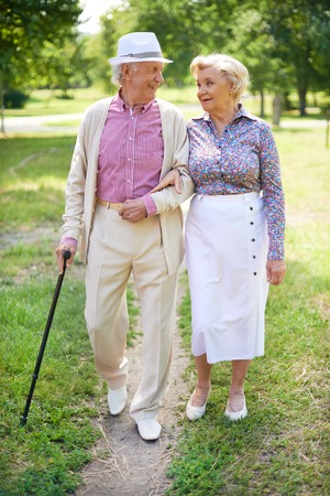 walk in: Happy seniors talking while taking a walk in the park Stock Photo