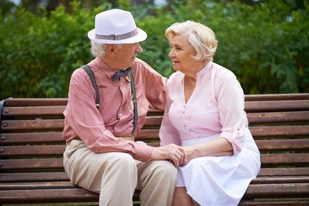 banc de parc: Aînés heureux de parler alors qu'il était assis sur un banc dans le parc Banque d'images