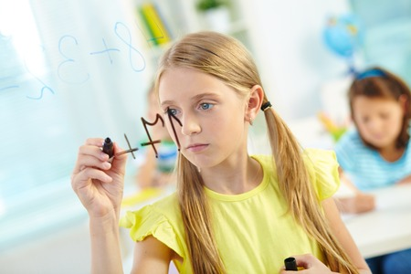 sums: Portrait of lovely girl doing sums on transparent board with schoolmates on background