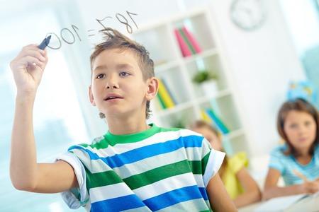 sumas: Retrato de muchacho inteligente haciendo sumas a bordo transparente con compa�eros de escuela en el fondo